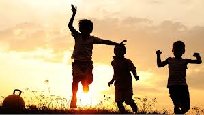 children playing in a field at sunset